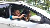 девочки : Two young women ride in a car and have fun. One of them takes a self photo on a film camera. Slow motion