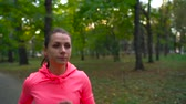 feminino : Running shoes - woman tying shoe laces and running through autumn park at sunset Vídeos