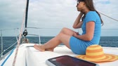 девочки : Woman in a yellow hat and blue dress rests aboard a yacht on summer season at ocean Стоковые видеозаписи