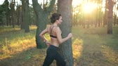feminino : Close up of woman with headphones running through an autumn forest at sunset. Slow motion