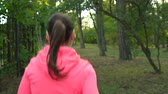 velocidade : Woman with wireless headphones and a smartphone chooses the music and runs through the autumn park
