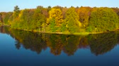над : Aerial view of the lake and the bright autumn forest on its shore. Forest is reflected on the surface of the lake