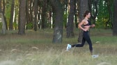 velocidade : Athletic woman running through an autumn forest. Slow motion Vídeos