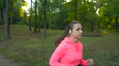 velocidade : Close up of woman with wireless headphones and a smartphone running through an autumn park at sunset Vídeos