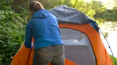 caminhadas : Woman is putting a tourist tent on the river bank