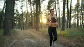 velocidade : Close up of woman with headphones running through an autumn forest at sunset Vídeos