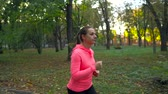 밀림 : Close up of woman running through an autumn park at sunset 무비클립
