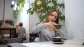 telemóvel : Beautiful woman spends her time in a cafe: rmakes photos for social networks - coffee and book