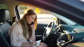 legrační : Business woman talking on a smartphone and taking notes in the daily sitting in the car Dostupné videozáznamy