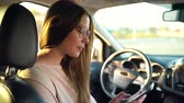 legrační : Woman in glasses speaks on the smartphone and drinks coffee in the car