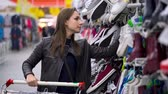 vyrobit : Woman chooses sports or home shoes in the supermarket Dostupné videozáznamy