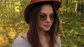 amarelo : Portrait of a beautiful smiling girl in a hat and sunglasses with a yellow maple leaf in the foreground in the autumn forest. Slow motion