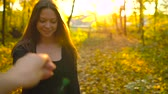 amarelo : Beautiful girl holds the hand of her boyfriend and follows him through the yellow autumn forest. Stock Footage