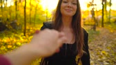 rood haar : Beautiful girl holds the hand of her boyfriend and follows him through the yellow autumn forest. Slow motion