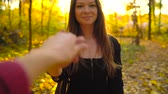 тянуть : Beautiful girl holds the hand of her boyfriend and follows him through the yellow autumn forest. Стоковые видеозаписи