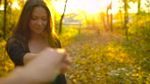 amarelo : Beautiful girl holds the hand of her boyfriend and follows him through the yellow autumn forest. Slow motion