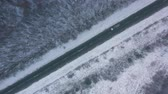 над : Aerial view of traffic on the road passing through the winter forest in severe weather Стоковые видеозаписи