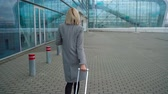 internationaal : Blonde girl rolls a suitcase near the airport terminal - view from the back. Slow motion Stockvideo