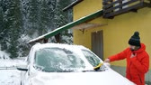 coberto : Man cleans the car from the snow near his house