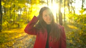 девочки : Portrait of a beautiful pensive girl in a red coat with a yellow maple leaf in the background in the autumn forest. Slow motion Стоковые видеозаписи