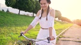 девочки : Young beautiful woman riding a bicycle at sunset