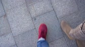 도시 : Top view of male legs in sneakers, which go along the sidewalk, meet female legs in boots and then walk together
