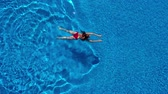 turkus : View from the top as a woman in a red swimsuit swims in the pool