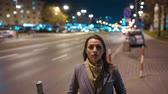 velocidade : Timelapse of woman standing still on crowded evening street while a blur of fast moving cars move behind her