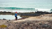 finish : Woman runs along the stony shore of the ocean. Healthy active lifestyle