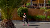 velocidade : Woman runs down the street among the palm trees. Healthy active lifestyle