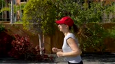 velocidade : Woman runs down the street among the palm trees. Healthy active lifestyle. Slow motion