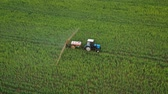agricultura : Aerial view of tractor treats agricultural plants on the field