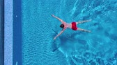 oynak : Aerial view of man in red shorts swims and and climbs out of the pool Stok Video