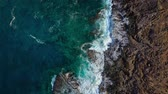 pedregoso : Top view of a deserted coast. Rocky shore of the island of Tenerife. Aerial drone footage of sea waves reaching shore