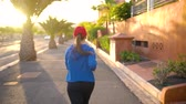 velocidade : Woman runs down the street among the palm trees at sunset, back view. Healthy active lifestyle