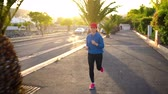 velocidade : Woman runs down the street among the palm trees at sunset. Healthy active lifestyle
