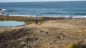 kamień : Woman runs along the stony shore of the ocean. Healthy active lifestyle