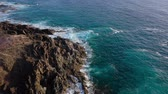pedregoso : View from the height of a deserted coast. Rocky shore of the island of Tenerife. Aerial drone footage of sea waves reaching shore