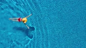 turkus : View from the top as a woman in a red swimsuit and a big yellow hat swims in the pool