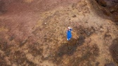 kamień : Aerial view of woman in a beautiful blue dress and hat stands on top of a mountain in a conservation area on the shores of the Atlantic Ocean. Tenerife, Canary Islands, Spain