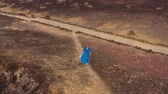 kamień : Aerial view of woman in a beautiful blue dress and hatwalking to the top of a mountain in a conservation area on the shores of the Atlantic Ocean. Tenerife, Canary Islands, Spain