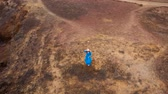 kamień : View from the height of woman in a beautiful blue dress and hat stands on top of a mountain in a conservation area on the shores of the Atlantic Ocean. Tenerife, Canary Islands, Spain