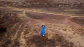 kamień : Aerial view of woman in a beautiful blue dress and hat stands on top of a mountain in a conservation area on the shores of the Atlantic Ocean. Tenerife, Canary Islands, Spain. Slow motion