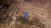 conservacion : Aerial view of woman in a beautiful blue dress and hat stands on top of a mountain in a conservation area on the shores of the Atlantic Ocean. Tenerife, Canary Islands, Spain. Slow motion