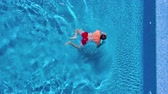 oynak : Aerial view of man in red shorts swims in the pool and get out of it Stok Video