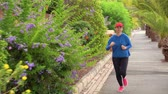 tory : Woman jogging along the street among the tropical alley Wideo