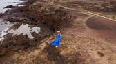 conservacion : Aerial view of woman in a beautiful blue dress and hat stands on top of a mountain in a conservation area on the shores of the Atlantic Ocean. Tenerife, Canary Islands, Spain