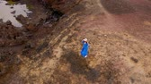 vista aérea : Aerial view of woman in a beautiful blue dress and hat stands on top of a mountain in a conservation area on the shores of the Atlantic Ocean. Tenerife, Canary Islands, Spain