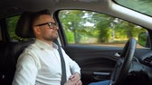 bir parçası : Bearded man in glasses and white shirt driving a car in sunny weather and uses autopilot function while driving