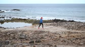 tory : Woman runs along the stony shore of the ocean. Healthy active lifestyle. Slow motion Wideo